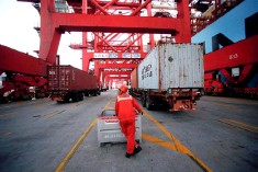 ??  ?? A worker is seen at the Yangshan Deep Water Port, part of the Shanghai Free Trade Zone, in Shanghai, China. Regional policy experts see increased protection­ism and trade wars as the top risks to growth in the Asia-Pacific. — Reuters photo