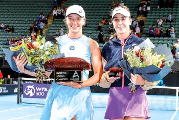 ?? - AFP photo ?? Iga Swiatek of Poland (L) poses with Switzerland's Belinda Bencic following Swiatek's victory in their women's singles final match at the Adelaide International tennis tournament in Adelaide.