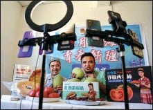 ?? DING LEI / XINHUA ?? Abdula Umur (right) livestreams with his father to sell Xinjiang specialties, including Hami melons and tomatoes, at a company in Turpan, Xinjiang Uygur autonomous region, on May 19.