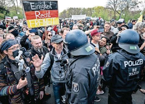 ?? FOTO: FABIAN SOMMER/DPA ?? Kein Abstand, kaum Masken: Demonstranten in Berlin werden von Polizisten abgedrängt. Rund 8000 Menschen waren zu der Demonstration gegen Corona-Maßnahmen gekommen, es flogen Steine und Flaschen. Die Polizei löste die Proteste auf.