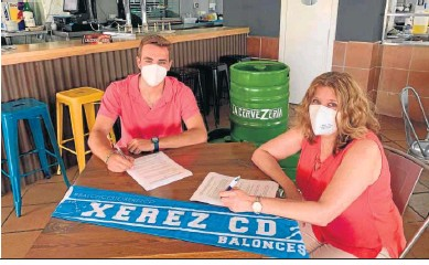 ??  ?? Quique Romero estampa su firma en el contrato ante Antonia Beltrán, presidenta del club.