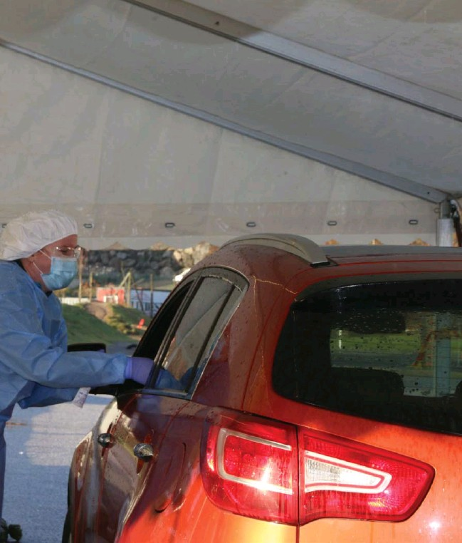 ??  ?? En helsemedarbeider tar prøve av en bilfører som har kjørt inn i teltet ved Lyngdalshallen. Erfaringene fra retestingen vil vaere nyttige dersom et nytt smitteutbrudd skulle oppstå.