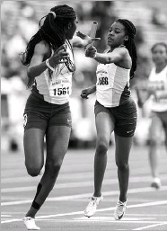 ?? Ashley Landis/ Staff Photographer ?? Desoto's Trinity Kirk (right) hands the baton to Rosaline Effiong during the 4x400 relay at the Texas Relays. DeSoto has the nation's best times in all three relays.