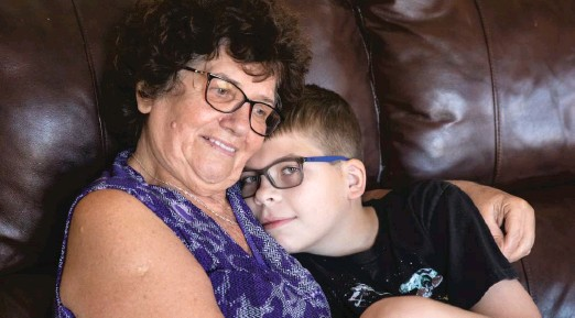 "?? ASHLEE REZIN GARCIA/SUN-TIMES ?? Danuta Kalinowska hugs her 12-year-old grandson Oliwier ""Oli"" Kluzik at their Northwest Side home last week."