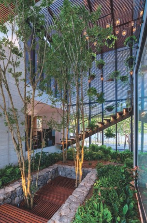 ??  ?? Left to right: Full height trees and lush greenery take pride of place in Teresa's interior courtyard; The floating staircase was crafted from steel mesh using the family's ship building expertise