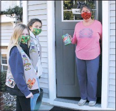 ?? PHOTO BY DOUG BISHOP ?? From left; Juliette Girl Scouts Ryleigh Gary, and Delaney Norris, both age 11, of Troop 446, deliver a box of Girl Scout cookies to neighbor Debbie Fogle of Stevensville. Girl Scout cookies are still being sold, though only following CDC guidelines to keep everyone safe during the pandemic. Orders are being taken individually, through the first Sunday in March. Both girls are wearing 'cookie masks' they made themselves!