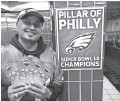 ?? MATT LISTON VIA AP ?? Eagles fan Jigar Desai poses with tickets to the Oct. 28 Eagles-Jaguars game in front of the subway pillar he ran into earlier this year in Philadelphia.