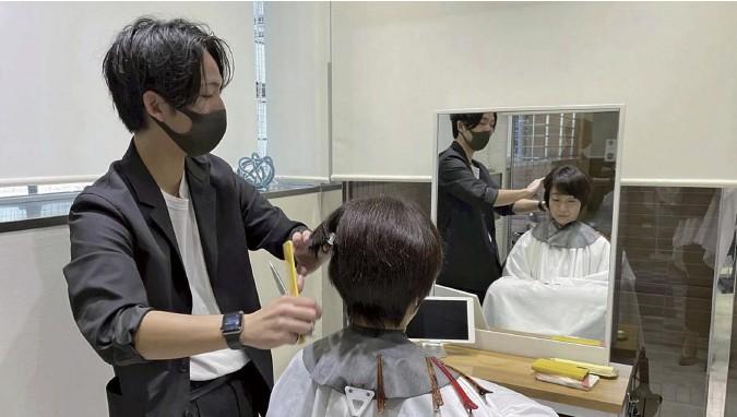 ?? The Yomiuri Shimbun ?? A beautician cuts a customer's hair at the The Bob & Short hair salon in the Jingumae district of Shibuya Ward, Tokyo.