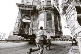 ?? Noah Berger / Associated Press ?? Workers pass a Victorian home Sunday as a truck pulls it through San Francisco. The house, built in 1882, was moved to a new location six blocks away.