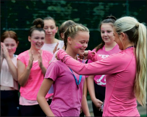 ??  ?? COMING TOGETHER PE teacher and lead Race for Life organiser, Miss James, awarding students their completion medals