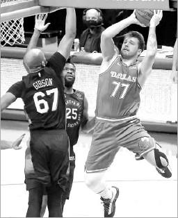 ?? Juan Figueroa/staff Photographer ?? New York Knicks center Taj Gibson jumps to block Mavericks guard Luka Doncic's shot in the first half at American Airlines Center.