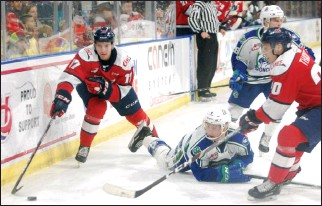 ?? Herald photo by Dale Woodard ?? Lethbridge Hurricanes forward Jett Jones and Swift Current Broncos defenceman Parker Hendren chase a loose puck along the boards while Canes forward Alex Thacker closes in during Western Hockey League action Saturday night at the Enmax Centre.