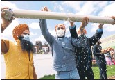 ?? JASON DECROW — THE ASSOCIATED PRESS ?? Jasbir Singh, left, and Vijay Singh wash a flagpole with milk as part of a ceremonial changing of the Sikh flag during Vaisakhi celebratio­ns at Guru Nanak Darbar of Long Island on Tuesday in Hicksville, New York.