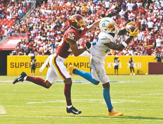?? RICKY CARIOTI/THE WASHINGTON POST ?? Chargers wide receiver Keenan Allen hauls in one of his nine receptions for 100 yards, both game highs, as Washington rookie cornerback Benjamin St-juste defends during the third quarter at Fedex Field.