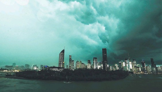 ??  ?? Storm clouds gather over Brisbane, turning the sky an eerie green. Picture: Liam Kidston
