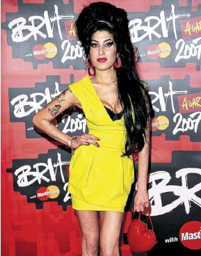 ?? PHOTOGRAPH: DAVE HOGAN/GETTY IMAGES ?? ▼ Amy Winehouse in the yellow Preen dress she wore to the 2007 Brit awards, with the red Moschino bag