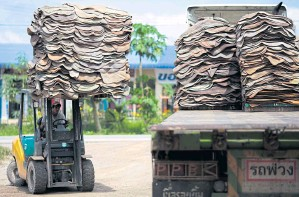 ?? PATIPAT JANTHONG ?? A man drives a forklift to unload rubber sheet at a market in Surat Thani province. Rubber producer Sri Trang is increasing production capacity to take advantage of rising demand.