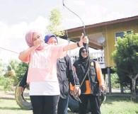 ??  ?? FOKUS: Mizma berkesempatan mencuba sukan memanah di lapang sasar sukan itu.