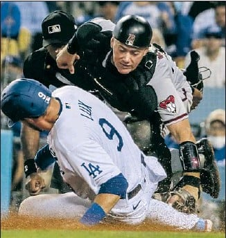 ?? Robert Gauthier Los Angeles Times ?? THE DODGERS' Gavin Lux is tagged out by Arizona Diamondbacks catcher Carson Kelly to complete a double play to end the fourth inning Monday night. The Dodgers won 5-1.