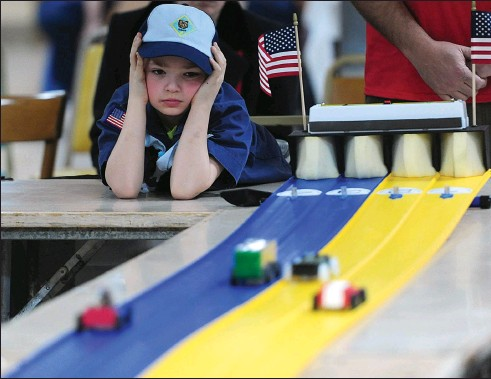 ?? Ernest A. Brown photo ?? Justin Cournoyer, 6, watches as his car finishes in one of the pinewood derby heats Saturday at Holy Family Church.