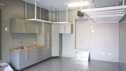 ?? OF ESPACE GARAGE PLUS PHOTO COURTESY ?? Plenty of cabinet space, overhead racks, a sink and work counter make for a neat and organized space in this Longueuil home garage.