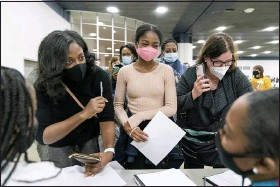 ?? DAVID GOLDMAN — THE ASSOCIATED PRESS ?? Denice Asbell, left, brings her daughter Rhegan, 13, center, down to the central counting board to observe democratic election challengers watching ballots being counted in the early morning hours of Wednesday, in Detroit.
