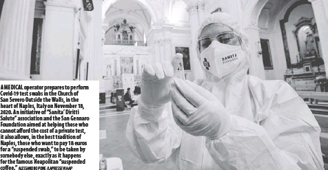 """?? Alessandro Pone /La Presse via AP ?? A medical operator prepares to perform Covid-19 test swabs in the Church of San Severo Outside the Walls, in the heart of Naples, Italy on November 18, 2020. An initiative of """"Sanita' Diritti Salute"""" association and the San Gennaro Foundation aimed at helping those who cannot afford the cost of a private test, it also allows, in the best tradition of Naples, those who want to pay 18 euros for a """"suspended swab,"""" to be taken by somebody else, exactly as it happens for the famous Neapolitan """"suspended coffee."""""""