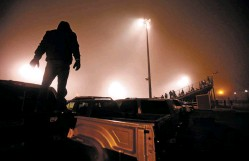 ?? LUIS SÁNCHEZ SATURNO/NEW MEXICAN FILE PHOTO ?? A Robertson fan watches a footbal game from the top of his truck at Robertson High School in 2015.