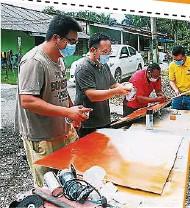 ??  ?? 姆鲁甘(右二)找来废置材料,自行绘制保护环境的告示牌,获得其余3名村主席的配合,左起和敬达、林德华,右为谢樟来。
