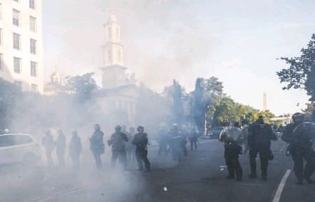 ?? ALEX BRANDON/ASSOCIATED PRESS ?? Tear gas floats in the air as police move protesters away from St. John's Church on June 1, 2020. The clearing occurred minutes before President Donald Trump arrived for a photo outside the church, but an inspector general report found it was part of a plan to build a fence.