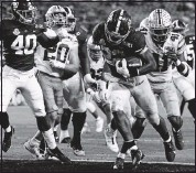 ?? THE ASSOCIATED PRESS ?? Alabama running back Najee Harris scores one of his three touchdowns against Ohio State on Monday night. Harris increased his season total to an SEC-record 30.