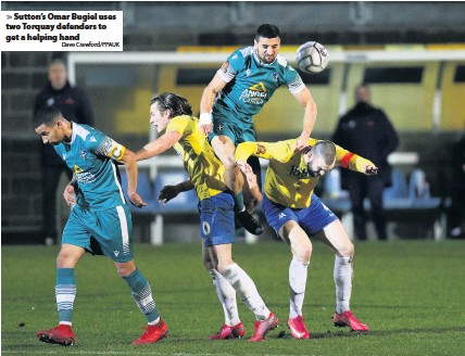 ?? Dave Crawford/PPAUK ?? Sutton's Omar Bugiel uses two Torquay defenders to get a helping hand