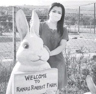 ??  ?? SERONOK: Salah seorang pengunjung merakam foto bersama replika arnab.