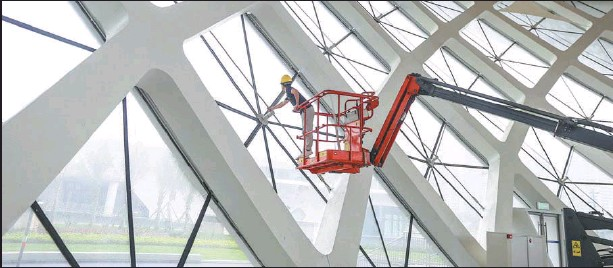 ?? GAO LIN / FOR CHINA DAILY ?? A worker installs window parts of the exhibition halls for the upcoming China International Consumer Products Expo at the Hainan International Exhibition Center on March 15. The first of such exhibitions will be held from May 7 to May 10.