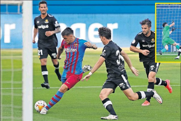 ??  ?? Rey Manaj, ante la presión de Iván de la Peña y la mirada de Fran Carbia, hace el 1-0 del Barcelona ante el Nàstic de Tarragona en el Estadio Johan Cruyff.