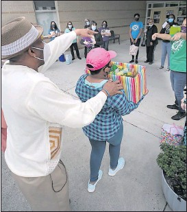 """?? BOB BROWN/TIMES-DISPATCH ?? Richmond fire Capt. Greg Johnson directed his granddaughter, Kayla Johnson-Brakett, 11, to begin distributing gifts to teachers at Henry D. Ward Elementary in Henrico County on Friday. """"I want the world to know what you all did,"""" Johnson said. """"It is truly a family and we are so blessed to have been part of your family."""""""