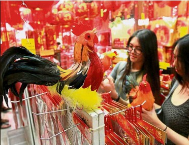 ??  ?? Shopping time: Customers browsing through rooster-themed decorative items at a shop in Kuala Lumpur. — SaM THaM/ The Star