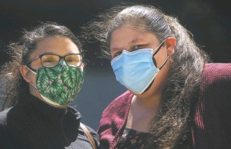 ?? Lea Suzuki / The Chronicle ?? Laurina Marcic (right), shown with sister Stephanie, is vaccinated but is still following safety precautions because she is worried about some of the family members with whom she lives.