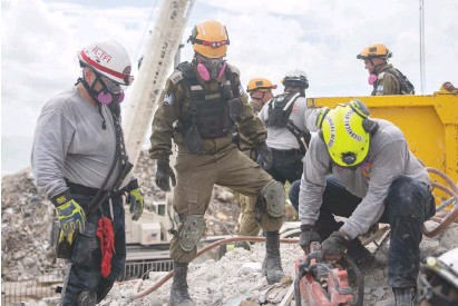 ?? (IDF) ?? IDF AND Miami-Dade Fire Rescue personnel work to clear rubble at the Champlain Towers site in Surfside, Florida, yesterday.