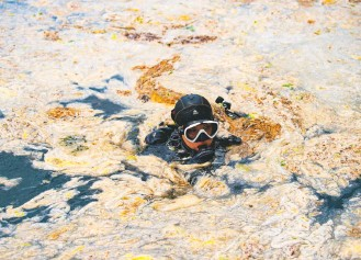 ?? YASIN Akgul/agence France-presse/getty Images ?? A diver inspects mucilage in waters off Istanbul. Scientists blame untreated sewage and other pollution but say rising water temperatures caused by climate change appear to be making the problem worse.