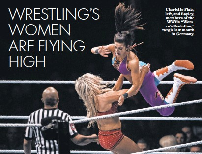 """?? LUKAS SCHULZE, BONGARTS/ GETTY IMAGES ?? Charlotte Flair, left, and Bayley, members of the WWE's """"Women's Evolution,"""" tangle last month in Germany."""