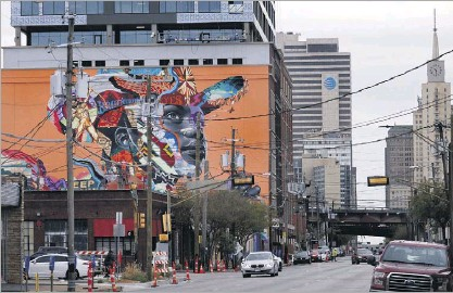 ?? Tom Fox/staff Photographer ?? A new 8,500square-foot mural by artist Tristan Eaton is painted on The Stack building in Deep Ellum in Dallas. The office and retail high-rise is to open in May.