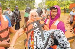 ??  ?? Elderly woman is rescued after being stranded in floodwaters Friday in western India.