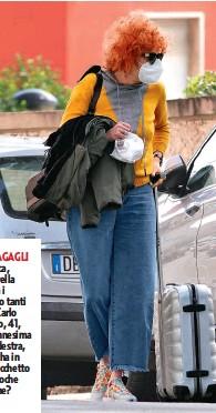 ??  ?? QUANTI BAGAGLI Borsa, giacca, trolley: Fiorella è carica, ma i bagagli sono tanti e il marito Carlo Di Francesco, 41, le passa l'ennesima tracolla. A destra, la cantante ha in mano un sacchetto di carta: brioche per colazione?