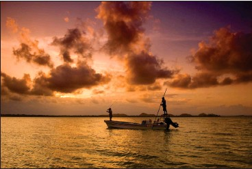 ??  ?? ABOVE: An angler casts his fly to a permit, while a guide poles, in the Bay of Honduras as the sun sinks behind the Maya Mountains in Punta Gorda, Belize.