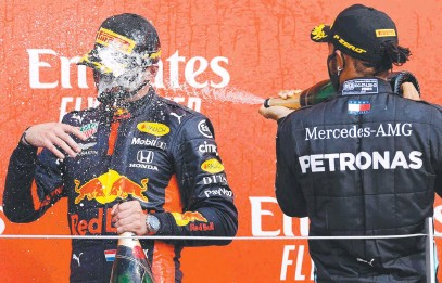 ??  ?? British driver Lewis Hamilton (right) sprays champagne at Max Verstappen after the Dutch star won the F1 70th Anniversary Grand Prix at Silverstone. Picture: AFP