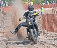 ?? MICHAEL SEARS / MILWAUKEE JOURNAL SENTINEL ?? A rider fights to stay upright in deep, soft sand as he heads into the pit area from the race track Friday at Bradford Beach.