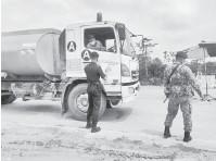 ??  ?? KETAT: Anggota polis, tentera dan RELA memeriksa dokumen perjalanan pemandu kereta dan lori pada sekatan jalan raya di Kilometer 18, Jalan Tatau-Sibu membabitkan sempadan bahagian Sibu dan Bintulu.
