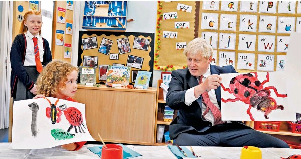 ??  ?? Boris Johnson compares paintings of ladybirds with a pupil on a visit to the Discovery School in West Malling, Kent. The Prime Minister announced an increase in pupil funding, with £2.2 billion more for schools in England