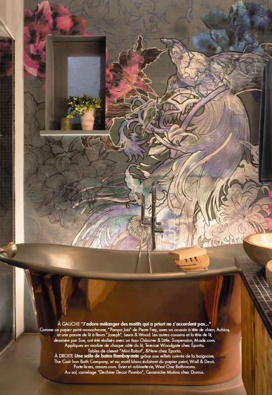"""??  ?? À GAUCHE """"J'adore mélanger des motifs qui a priori ne s'accordent pas…"""" Comme ce papier peint monochrome, """"Pampa Jais"""" de Pierre Frey, avec un coussin à tête de chien, Achica, et une parure de lit à fleurs """"Joseph"""", Lewis & Wood. Les autres coussins et la tête de lit, dessinée par Sue, ont été réalisés avec un tissu Osborne & Little. Suspension, Made.com. Appliques en marbre de chaque côté du lit, Terence Woodgate chez Eporta. Tables de chevet """"Mini Robot"""", &New chez Eporta. À DROITE Une salle de bains flamboyante grâce aux reflets cuivrés de la baignoire, The Cast Iron Bath Company, et au motif blanc éclatant du papier peint, Wall & Decò. Porte-livres, amara.com. Évier et robinetterie, West One Bathrooms. Au sol, carrelage """"Dechirer Decor Piombo"""", Ceramiche Mutina chez Domus."""